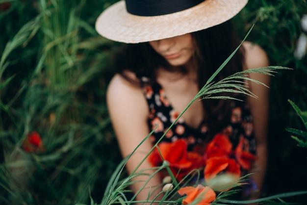 Close-up portret pięknej bezpłatnej dziewczyny w kapeluszu w letnim polu czerwonych maków