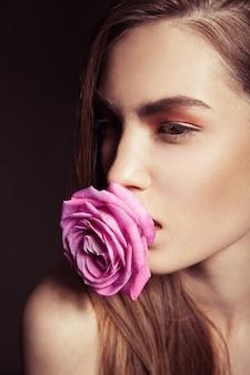 Close-up portret pięknej brunetki z różową różą