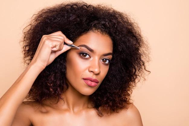 Close-up portret pięknej dziewczyny poważne za pomocą metalowych kleszczy do stylizacji brwi