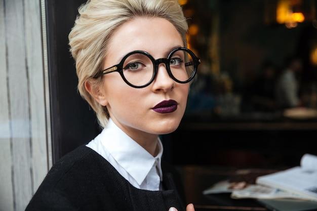 Close-up portret pięknej dziewczyny w okularach i siedzącej w kawiarni