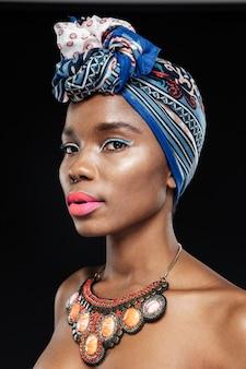 Close-up portret pięknej kobiety w chuście na głowie odizolowanej na czarnej ścianie