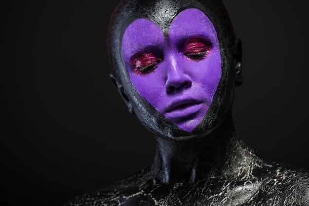 Close-up portret pięknej kobiety ze sztuką ciała na twarzy w kolorze czarnym z fioletowym sercem na czarnej ścianie