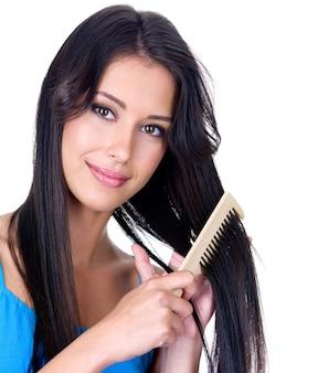 Close-up portret pięknej ładnej kobiety z grzebieniem, dbając o jej długie włosy - na białym tle