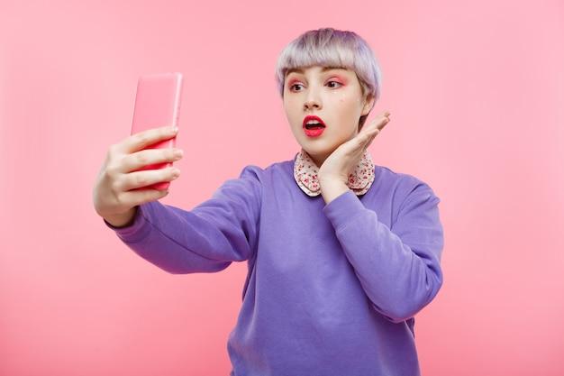 Close-up portret pięknej lalki dziewczyny z krótkimi jasnofioletowymi włosami na sobie liliowy sweter co selfie na różowej ścianie