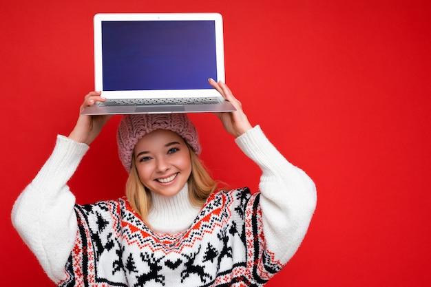 Close-up portret pięknej młodej kobiety posiadania komputera laptop z pustym ekranem monitora z makiety na sobie czapkę z dzianiny zimowej i sweter patrząc na kamery na białym tle nad czerwonym tle ściany.
