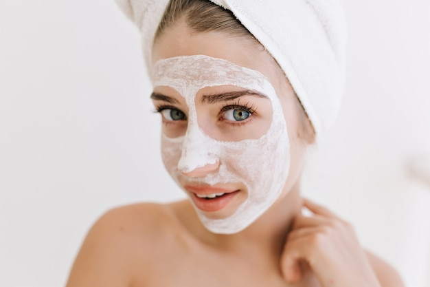 Close-up portret pięknej młodej kobiety z ręcznikami po kąpieli zrobić maseczkę kosmetyczną na jej twarzy.