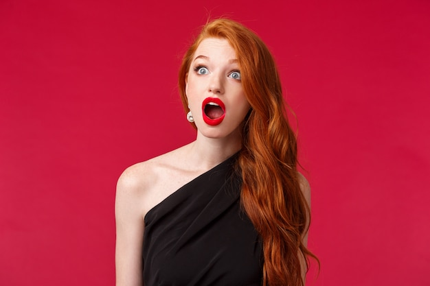 Close-up portret pod wrażeniem młodej rudowłosej dziewczyny bez słowa w czarnej sukience, czerwonej szmince, patrzy w lewo z wyłupiastymi oczami i opuszczoną szczęką, dysząc, powiedz wow, stojąca czerwona ściana