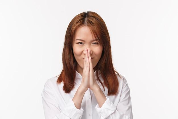 Close-up portret podekscytowanej i pewnej siebie młodej kobiety z azji, trzymaj ręce w modlitwie przy twarzy, wyglądając na zdeterminowanego, modląc się lub żebrząc, potrzebujesz pomocy błagając, błagając o przysługę