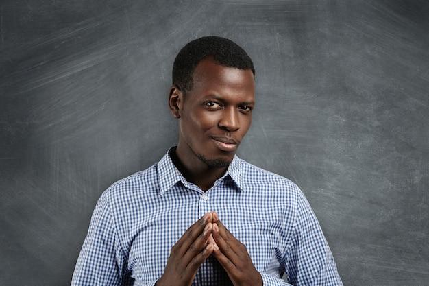 Close-up portret podstępnego, przebiegłego, podstępnego młodego studenta lub pracownika, który próbuje coś spiskować lub kogoś pieprzyć, odizolowany na tablicy.