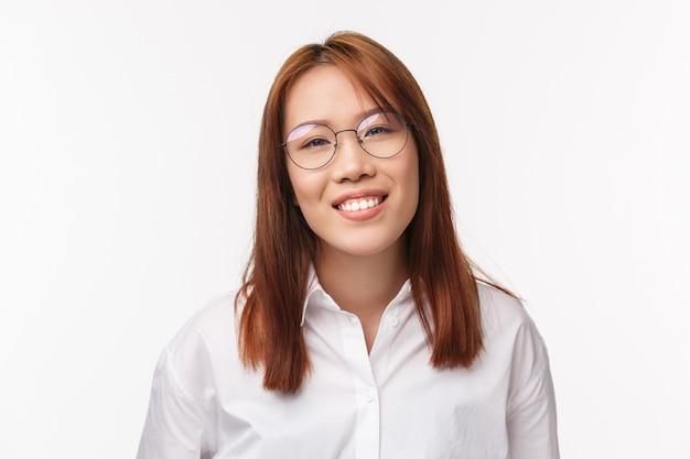 Close-up portret przyjaznej i wesołej azjatyckiej kobiety przedsiębiorcy w przepisanych okularach, pokazujący promienny uśmiech, wyglądający na zadowolonego i beztroskiego, gotową pomoc klienta, stojącą białą ścianę