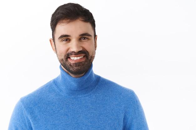 Close-up portret przystojnego, odnoszącego sukcesy biznesmena z brodą, uśmiechniętego szczęśliwego i usatysfakcjonowanego, wyrażającego entuzjazm i pozytywność, pozostającego po jasnej stronie, stojącego radosnej białej ściany