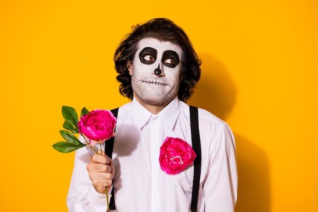 Close-up portret przystojny przerażający złowrogi nieśmiały wesoły facet trzymający w ręku pojedynczy naturalny świeży róża kwitnący kwiat pierwsza data amour na białym tle jasny żywy połysk żywy żółty kolor tła