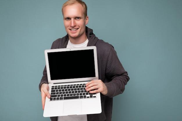 Close-up portret przystojny uśmiechnięty blondyn trzymając komputer laptopwith pusty ekran monitora z makiety i kopiować przestrzeń patrząc na kamery na białym tle na niebieskim tle.