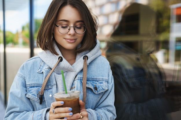 Close-up portret romantycznej wspaniałej dziewczyny w okularach i dżinsowej kurtce, rozmarzonej patrząc na filiżankę kawy, pijącej lodową latte i uśmiechającej się szczęśliwie, czując ciepło i szczęście spacerując na świeżym powietrzu.