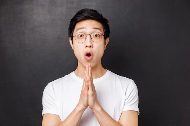 Close-up portret rozbawionego, entuzjastycznego młodego mężczyzny azjatyckiego, trzymaj ręce w modlitwie, splataj dłonie razem, prosząc o coś, prosząc o pomoc lub radę, powiedz proszę, wdzięczny za wysiłek przyjaciela