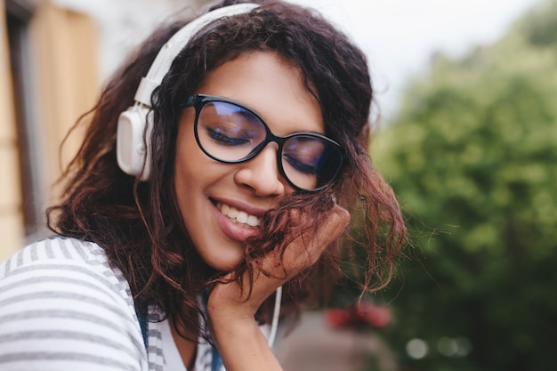 Close-up portret rozmarzonej młodej damy o jasnobrązowej skórze, cieszącej się ulubioną piosenką