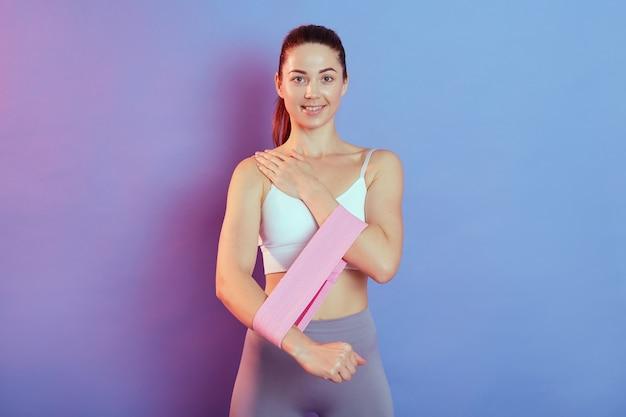 Close-up portret sportowej kobiety z pięknym wyszkolonym ciałem ćwiczyć mięśnie rąk. ładna kobieta trenująca z opaską, pracujące ręce, ubrana w biały top.