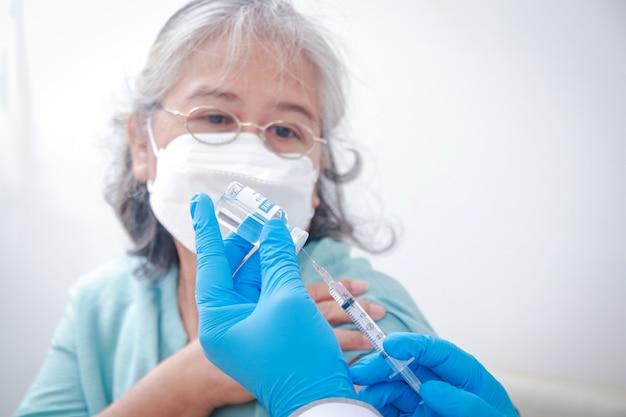 Close-up portret starszej kobiety otrzymującej szczepienia przeciwko koronawirusowi od lekarza płci męskiej w niebieskich rękawiczkach aby wzmocnić układ odpornościowy, aby zapobiec zakażeniu. szczepienia osób starszych