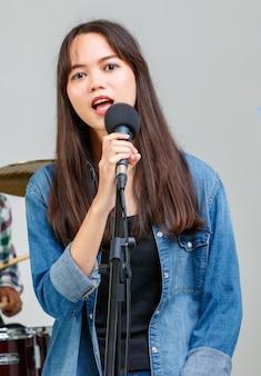 Close-up portret strzał tajsko-turecki nastoletni piosenkarz śpiewający piosenkę z mikrofonem, patrząc w kamerę. profesjonalna praktyka wokalna młodszego studenta z zespołem. koncepcja prób