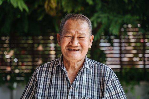 Close-up portret szczęśliwego azjatyckiego starszego mężczyzny śmiejącego się