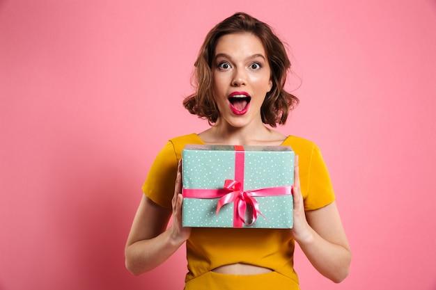 Close-up portret szczęśliwej wychodzącej ładnej brunetki kobiety trzymającej pudełko,