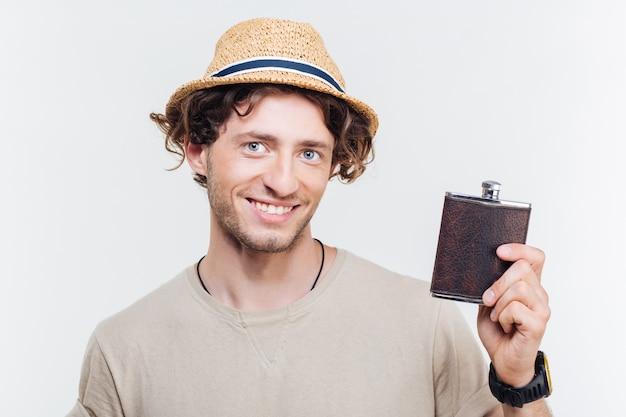 Close-up portret szczęśliwy młody człowiek trzyma kolbę alkoholu na białym tle na białym tle