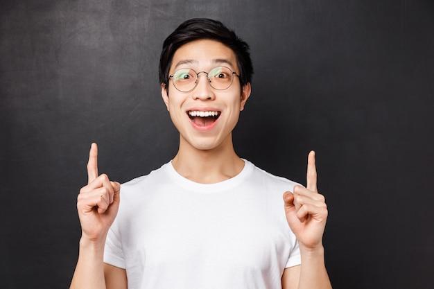 Close-up portret szczęśliwy zaskoczony i podekscytowany młody azjatycki facet widząc cud coś naprawdę niesamowitego, wskazując palcami w górę, uśmiechając się pod wrażeniem i wpatrując się w zdumienie