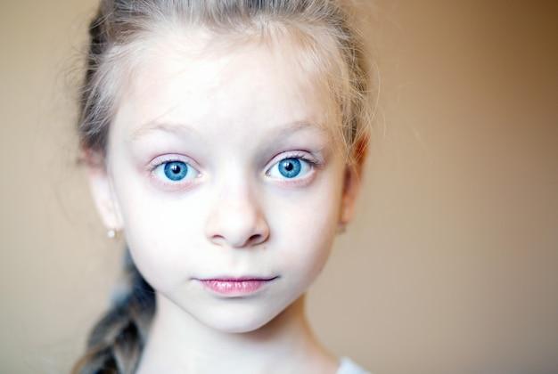 Close-up portret twarzy 8-letniej pięknej dziewczyny, z dużymi niebieskimi oczami i blond włosami, emocjonalnie patrzy w ramkę