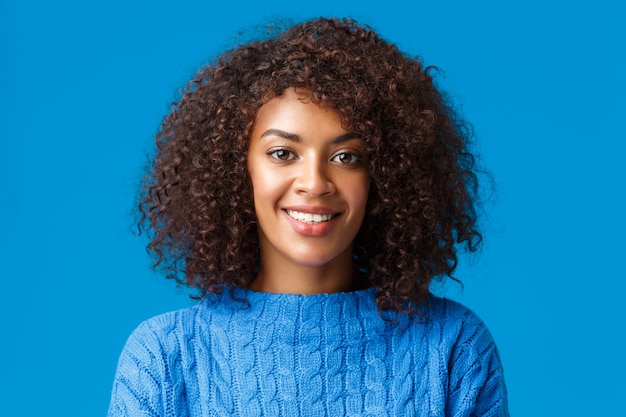 Close-up portret urocza młoda afroamerykańska kobieta z kręconymi fryzurami w stylu afro, uśmiechnięta z radosnym przyjemnym wyrazem, ciesząca się zimowymi wakacjami, ubrana w sweter, niebieska ściana.