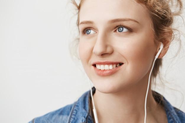 Close-up portret uroczej europejskiej rudej dziewczyny patrząc na bok z pewnym siebie i miłym wyrazem podczas słuchania muzyki