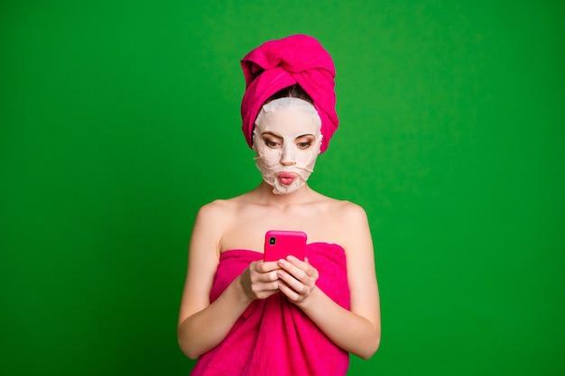 Close-up portret uroczej skupionej kobiety noszącej turbanową maskę na twarz, używając urządzenia wydętych ust, rozmawiających na jasnozielonym tle
