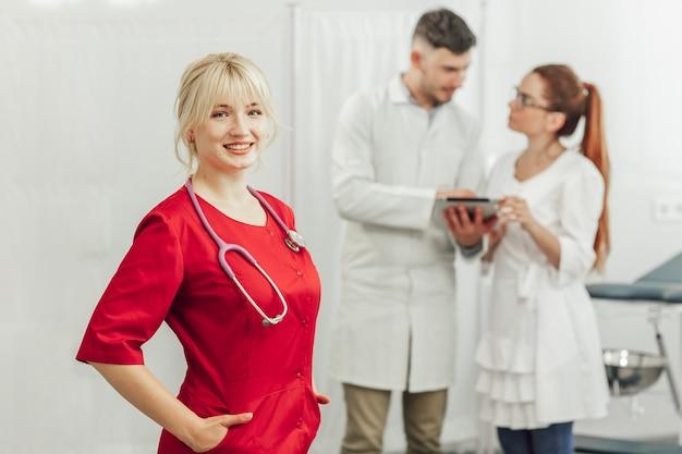 Close-up portret uśmiechniętego lekarza kobiet w czerwonym mundurze ze stetoskopem