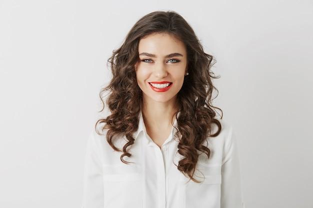 Close-up portret uśmiechniętej atrakcyjnej kobiety z białymi zębami, długimi kręconymi włosami, czerwoną szminką makijaż patrząc w kamerę na białym tle na sobie białą bluzkę