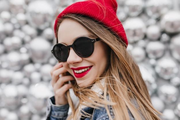 Close-up portret uśmiechniętej niesamowitej dziewczyny nosi czarne okulary. urocza młoda dama w czerwonym kapeluszu pozuje w pobliżu kulek dyskotekowych i dotyka jej włosów.