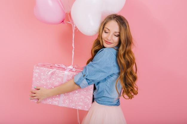 Close-up portret wdzięcznej kręconej dziewczyny z uroczą twarzą trzymającą prezent i balony na urodziny przyjaciela. urocza długowłosa młoda kobieta z zamkniętymi oczami w stylowym stroju otrzymała prezent na przyjęciu