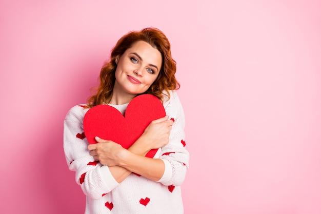 Close-up portret wesoła słodka delikatna dziewczyna na sobie biały sweter obejmujący duże serce