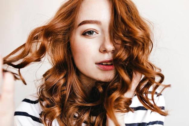 Close-up portret wspaniałej dziewczyny z zainteresowaną twarzą stojącą. kryty strzał niesamowitej kobiety bawiącej się lśniącymi rudymi włosami.