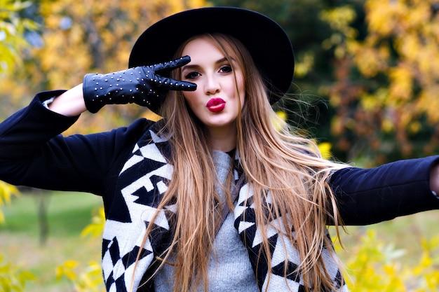 Close-up portret wspaniałej pani w czarnym kapeluszu, wygłupiać się podczas jesiennej sesji zdjęciowej. zabawna młoda dama w eleganckich rękawiczkach spędza czas w parku w dzień września.