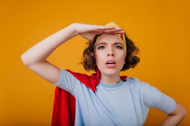 Close-up portret zabawnej superwoman pozuje emocjonalnie na żółtej przestrzeni