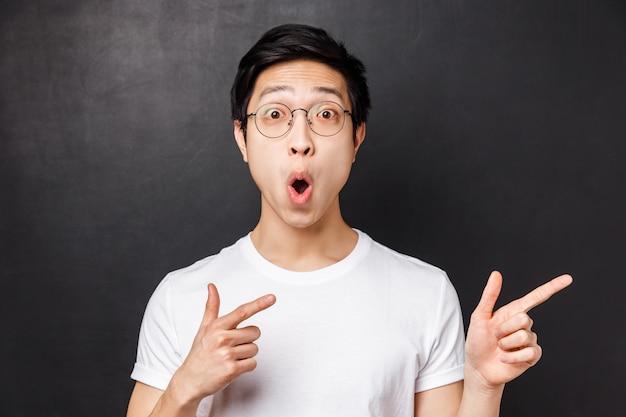 Close-up portret zachwyconego i rozbawionego azjatyckiego młodzieńca w białej koszulce, z otwartymi ustami zdziwiony, powiedz wow, wskazujący palcami na coś imponującego i oszałamiającego,