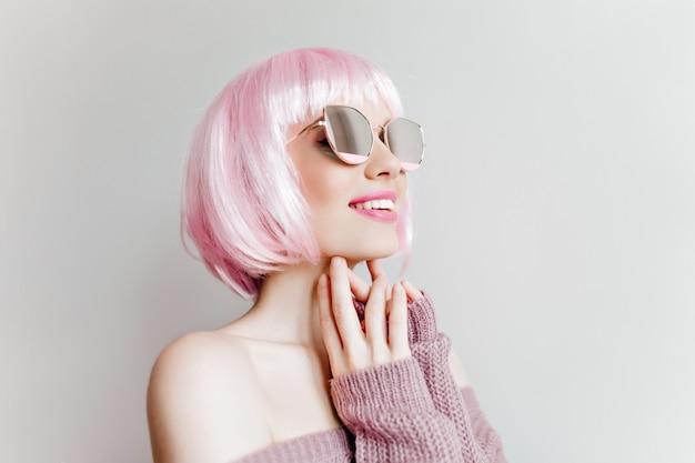 Close-up portret zainteresowanej modnej dziewczyny w stylowym peruke. kryty zdjęcie uroczej kobiety w błyszczących okularach przeciwsłonecznych