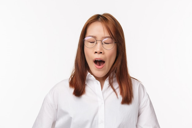 Close-up portret zmęczonej azjatyckiej pani biurowej, kobieta ziewająca z zamkniętymi oczami, wczesne budzenie się, przedsiębiorca potrzebuje kawy, aby uzyskać energię, nosić okulary, pracować nad projektem do późna, stać