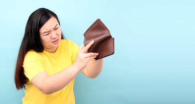 Close-up portret zszokowanej, zaskoczonej zaniemówionej kobiety azji, trzymającej pusty portfel na niebieskim tle w studio