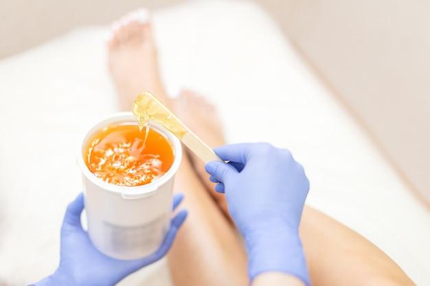 Close-up ręce kosmetyczki w niebieskie rękawiczki gospodarstwa wklej dla słodzenia depilacji
