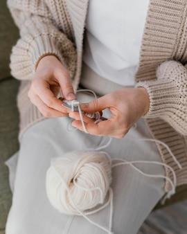 Close-up ręce na drutach z białą przędzą