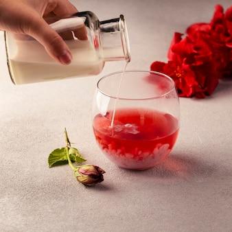 Close-up ręcznie wlewając syrop do herbaty