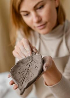 Close-up rozmyta kobieta trzyma gliniany liść