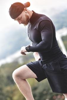 Close-up shot brodaty mężczyzna sportive po sesji treningu sprawdza wyniki fitness. dorosły facet w opasce sportowej z trackerem.