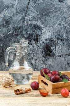 Close-up śliwki w drewnianej skrzyni z dzbankiem wody, cynamonu i szotów na drewnianej powierzchni. wolne miejsce w pionie na tekst
