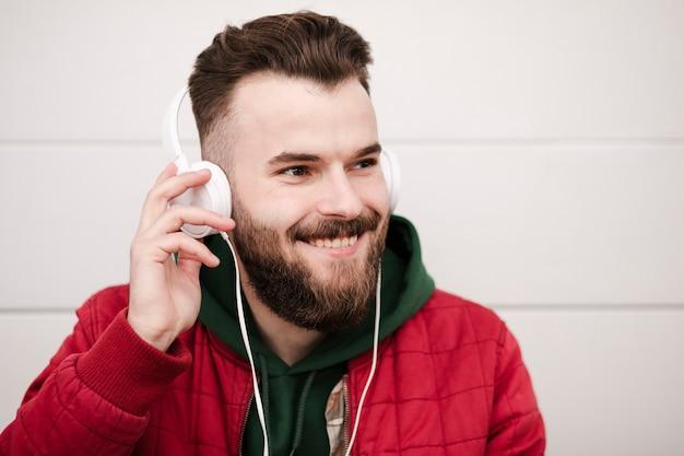 Close-up smiley facet ze słuchawkami i brodą